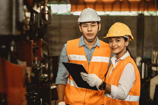 Engineer team male working with women work help support together in heavy industry teach and training machine operation in factory
