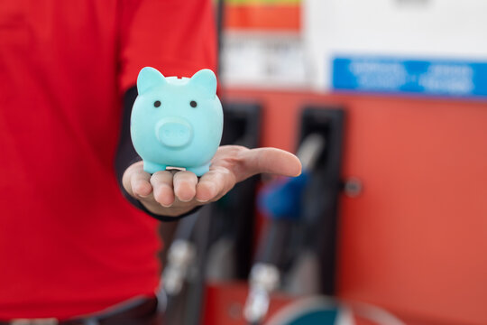 Gas station staff worker with piggy bank for save money from low fuel price, gas costs reduction, cut and saving gasoline drop price concept.