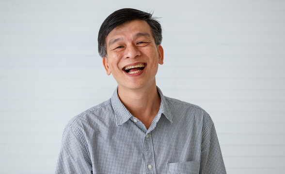 Portrait of warm personality senior older Asian man in casual dress friendly pose and laughing with happy and successful feeling and self-confident