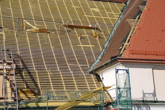 Mit Bieberschwanz Ziegeln wird das Steildach einer Kirche von einer Dachdeckerfirma erneuert.