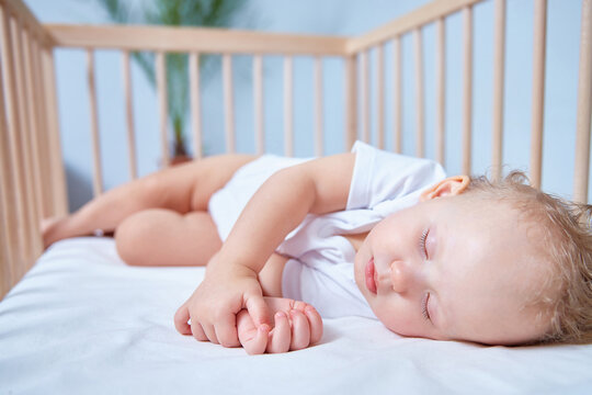 A cute baby in white clothes sleeps in a wooden crib in a bright, spacious room.