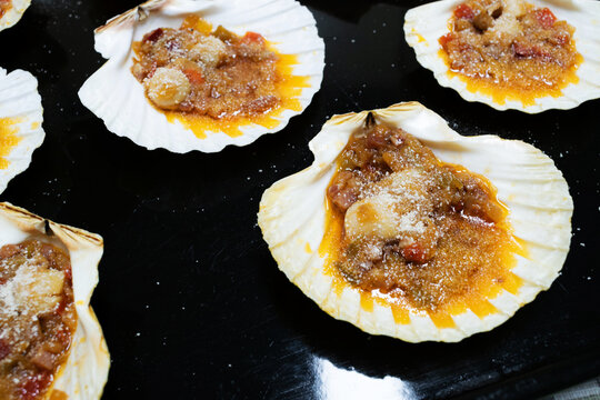 View of a Scallops with onion, pieces of ham, pepper, tomato sauce and breadcrumbs. Scallops Galician