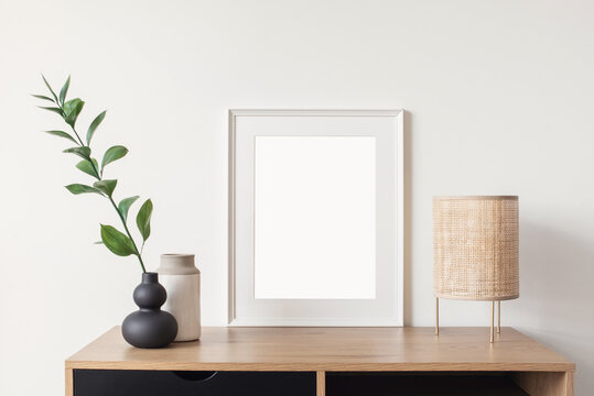 Blank picture frame mockup in home interior design. Living room, commode with lamp and vases. View of modern scandinavian style interior with artwork template on a white wall.