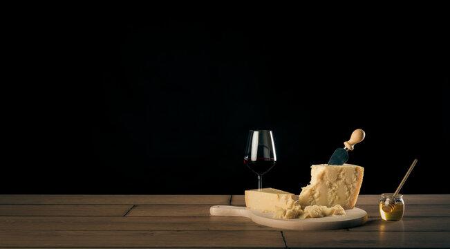 Tavola imbandita con due bicchieri di vino rosso, formaggio parmigiano reggiano su un tagliere con coltello e miele in un contenitore di vetro con dosatore.