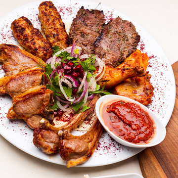 White plate with different types of meat prepared on the grill by special Turkish recipe. Delicious kebab plate with spices and lavash. Meat prepared on the barbeque with special sauce.