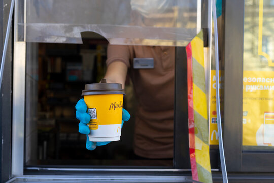 McDonalds worker holding cup of coffee to go in hand  through the window of mcdonalds car drive thru service.