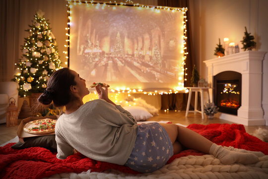 MYKOLAIV, UKRAINE - DECEMBER 24, 2020: Woman watching Harry Potter and Philosopher's Stone movie via video projector in room. Cozy winter holidays atmosphere