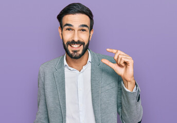 Fototapeta Young hispanic man wearing business clothes smiling and confident gesturing with hand doing small size sign with fingers looking and the camera. measure concept. obraz