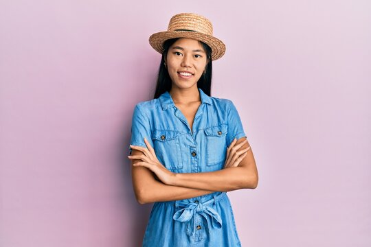 Young chinese woman wearing summer hat happy face smiling with crossed arms looking at the camera. positive person.