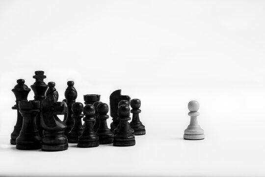 Todas las piezas negras se enfrentan a un solo peón blanco sobre fondo blanco infinito