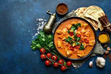 Chicken tikka masala - traditional dish of indian cuisine in a black bowl.Top view with copy space.