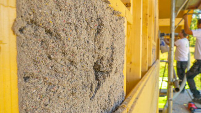 CLOSE UP: A group of workers blow cellulose insulation into the wooden walls.