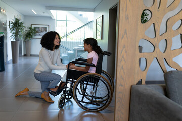 Happy mixed race mother kneeling holding hands talking with daughter in wheelchair in hospital foyer