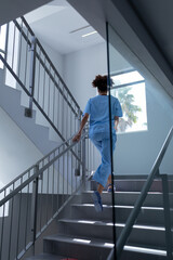 Rear view of mixed race female doctor wearing scrubs running up stairs in hospital