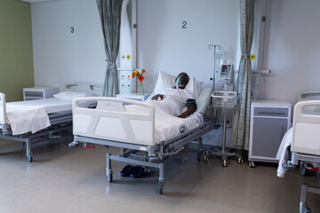 African american male patient lying on hospital bed wearing oxygen mask ventilator