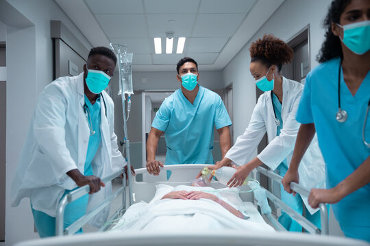 Mixed race doctors wearing face masks transporting patient in hospital bed