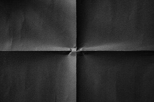 Black paper folded in four fraction background