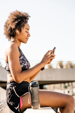 Athlete woman using her mobile phone outdoors.