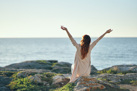 woman in a sweater gestures with her hands over her head in the mountains near the sea fresh air
