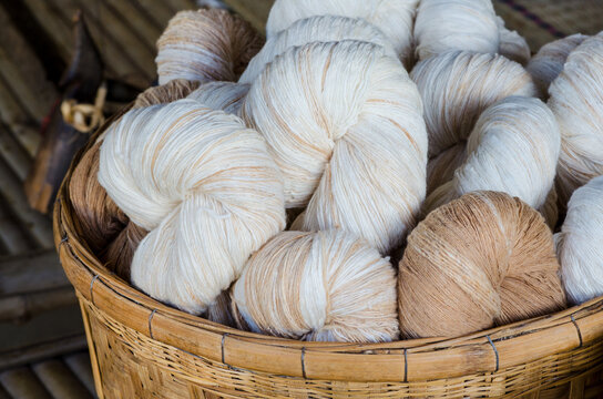 Closed up natural soft white and brown cotton thread bundle in wooden basket ready for fabric or cloth production