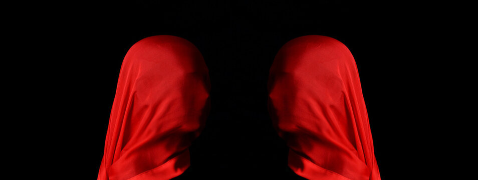 Two mannequin heads with large red silk scarf, facing each other, black background.