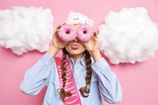 Indoor shot of cute young woman keeps lips folded covers eyes with tasty delicious doughnuts dressed in casual clothes poses against pink background. People unhealthy food and temptation concept