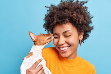 Friend of family. Close up shot of happy curly haired woman plays with dog expresses positive emotions likes animals. Small pedigree puppy licks face of owner. Adopted pet. Tender sincere feelings