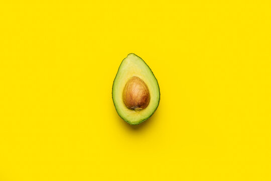fresh ripe half of an avocado with a bone on a bright yellow background. Top view, flat lay