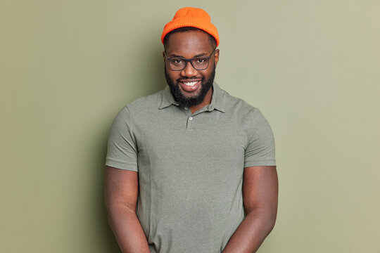 Handsome black bearded man smiles happily looks self confident at camera enjoys good day and pleasant talk wears basic t shirt orange hat and spectacles poses against dark green studio background