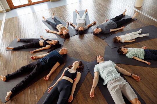 View of a big group of young people laying on yoga mat in a circle, stretching in a yoga class