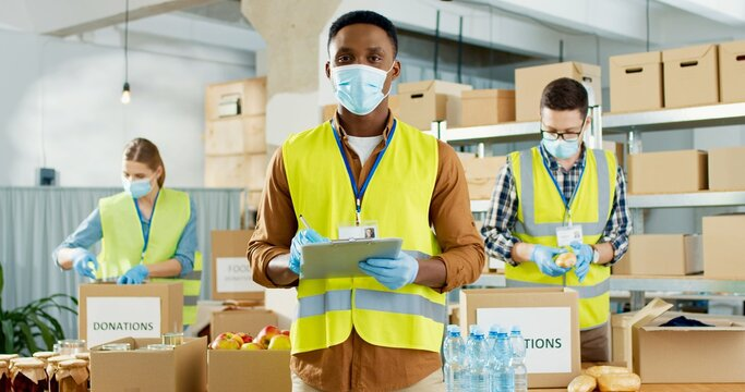 Portrait of young African American male social worker in medical mask standing in warehouse checking donation list looking at camera Caucasian volunteers in uniform preparing parcels, covid-19 concept