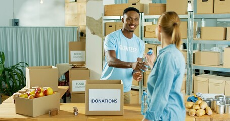 Fototapeta Happy African American young handsome man volunteer smiling working at charity center giving food to poor people. Social help, donations and volunteering. social work, humanitarian help obraz