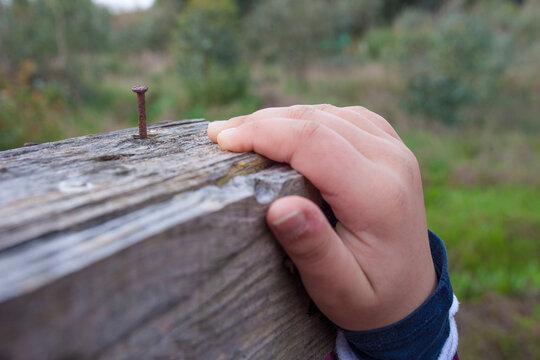 Child boy hand grabbing a board with rusty nail near