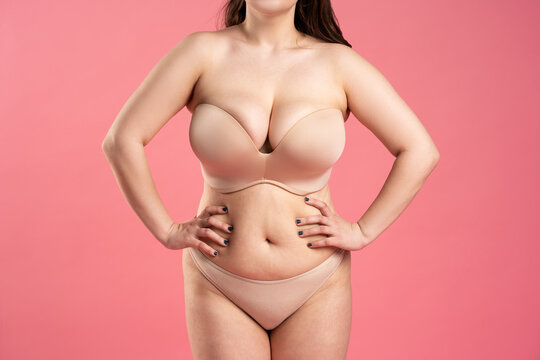 Fat woman with large breasts in a push-up bra on pink background, overweight female body
