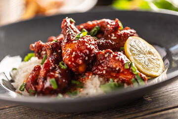 Marinated glazed sticky chicken thighs with seesame served with rice and coriander