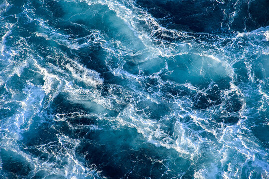 Stormy ocean waves backlit by the light of the setting sun. Transparent. Navy blue. Blue. Background. Pattern.