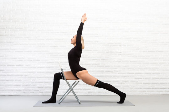 Iyengar yoga indoor with a chair. Sexy fit caucasian woman in black tight-fitting body and gaiters does warrior pose using a stool.