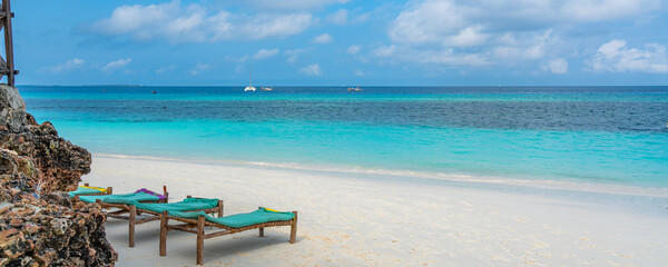 Tropical white beach with bench on Zanzibar island. Tanzania.