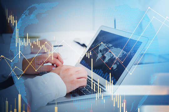 Businessman trader hands working with laptop. Stock market changes, business candlesticks graph chart. Double exposure of earth map and lines. Concept of internet trading