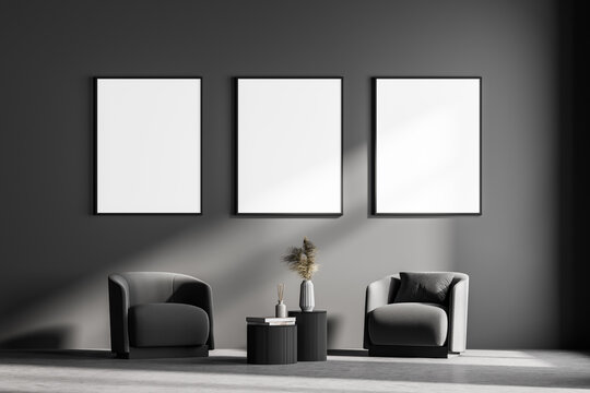 Modern living room interior with two armchairs and small table. Three mock up framed posters on grey wall. Reading and relax concept. No people. 3d rendering.