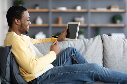 Cheerful african american man with credit card and digital tablet
