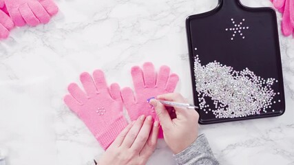 Wall Mural - Time lapse. Flat lay. Rhinestone pink kids gloves with snowflake shapes.