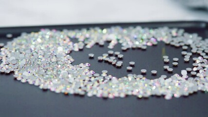 Wall Mural - An abundance of white rhinestones with flat back on a black board ready for a craft project.