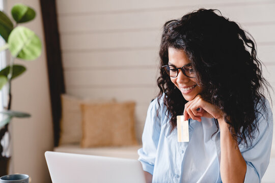Young african businesswoman doing shopping online using laptop and credit card. African-american woman doing orders through the Internet