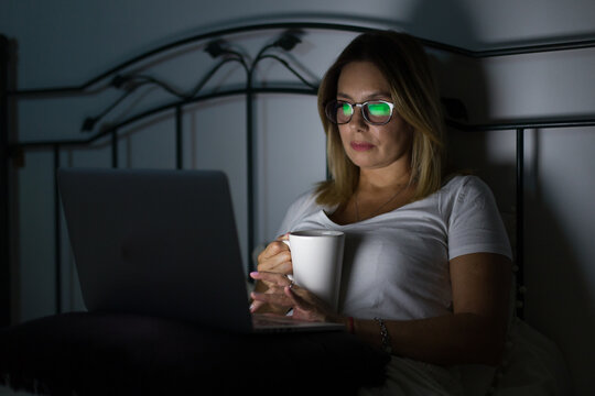 beautiful woman uses computer in bed at night with a mug