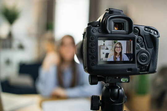 Smiling female influencer using modern camera for leading live stream while sitting at home. Focus on screen of video camera. Concept of people and technology.