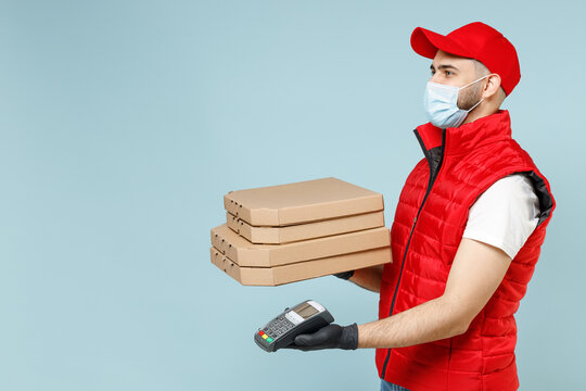 Delivery guy employee man in red cap white tshirt vest uniform sterile face mask gloves work courier service on lockdown covid-19 flu hold pizza in flatbox terminal isolated on pastel blue background.