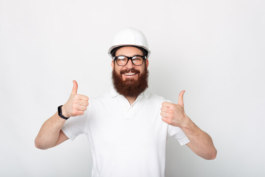 We are the best in our work. Bearded man is wearing a hard hat showing thumbs up.