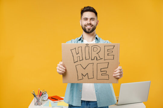 Young happy smiling employee business man wearing shirt stand work white office desk pc laptop hold cardboard sign card need job hire me looking camera isolated on yellow background studio portrait.