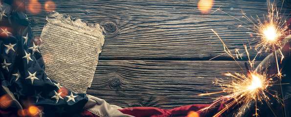 Fototapeta Independence Day - United States Declaration of Independence And Flag On Rustic Wooden Table Background With Sparklers